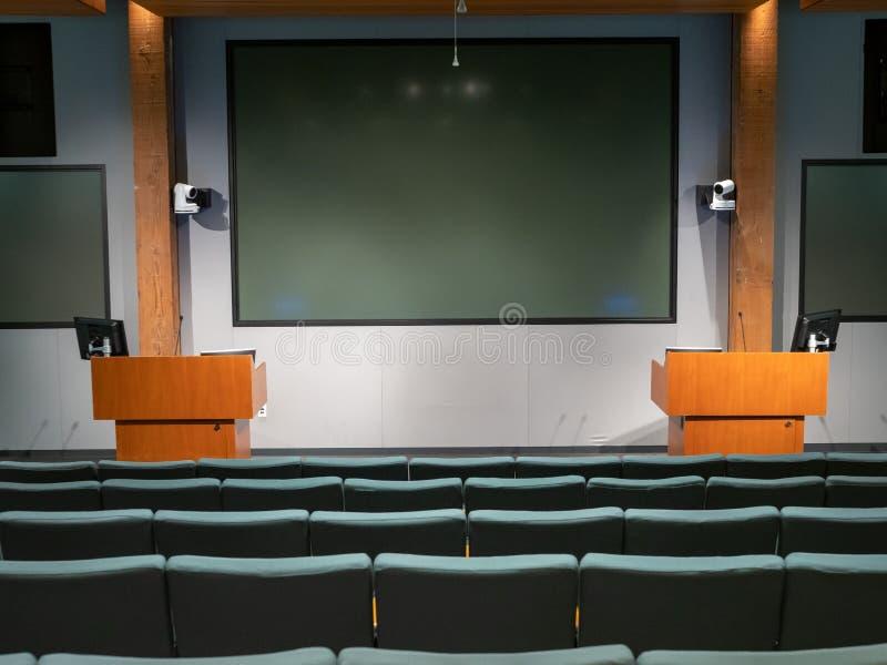 Auditorio oscuro encendido de la oficina con los podios dobles y las exhibiciones multi del proyector foto de archivo libre de regalías