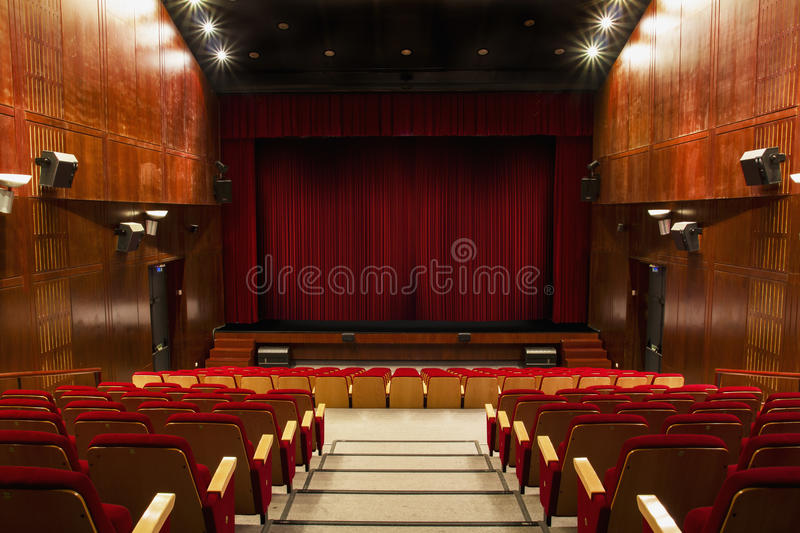 Auditorium with red chairs. And red curtain stock images