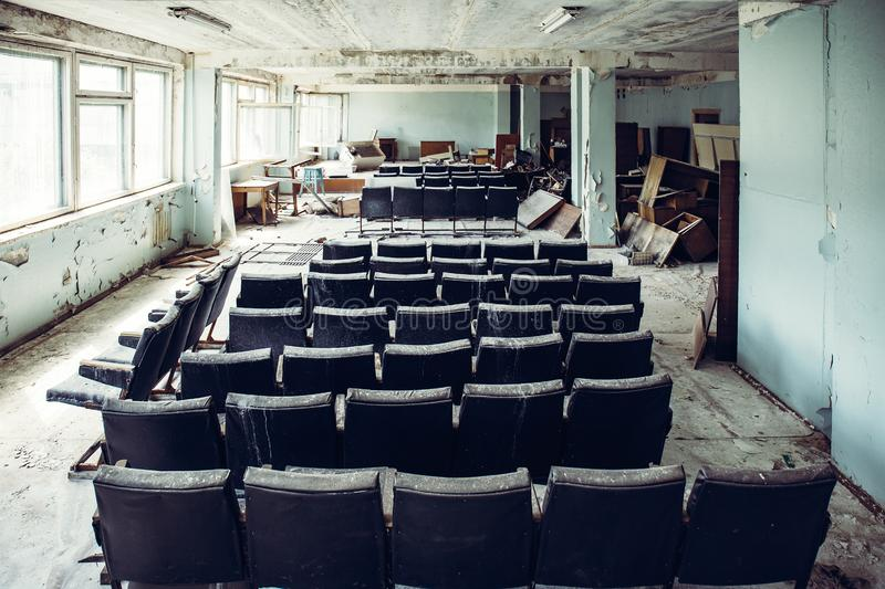 Auditorium room with chairs in abandoned and ruined industrial factory, creepy aged building after war, no people. Toned stock images