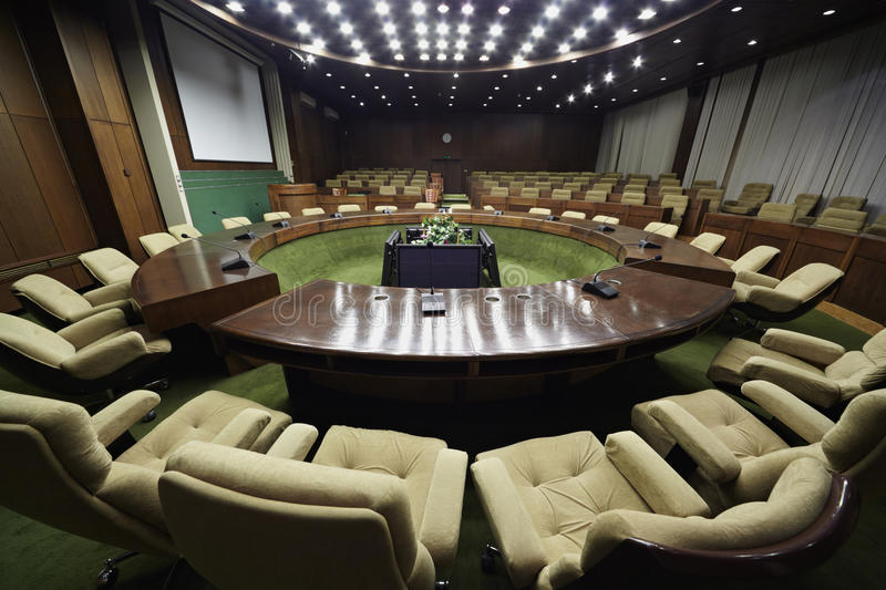 Auditorium with round table and armchairs stock image