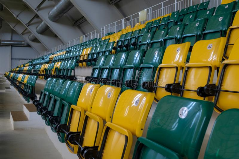 The auditorium in the sports complex with green and yellow plastic seats. Places for spectators of a sports match indoors. The royalty free stock image