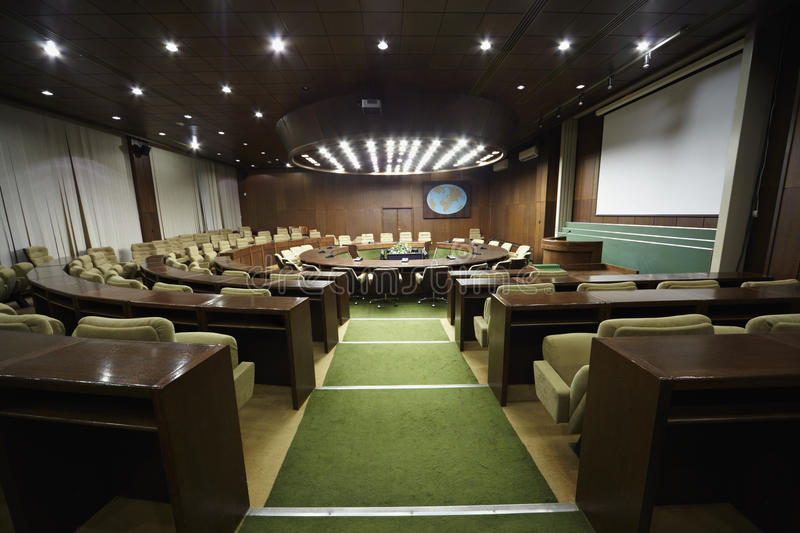 Auditorium with table and armchairs around it.