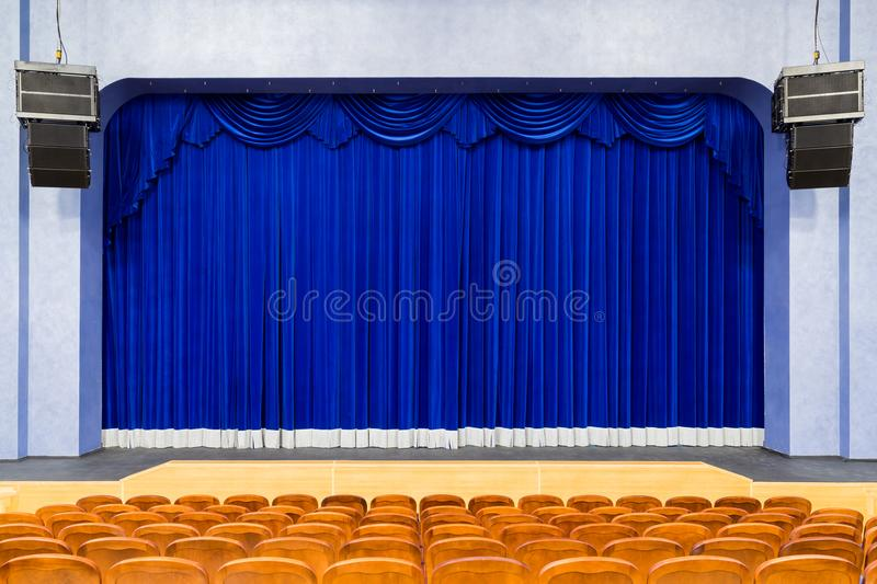 The auditorium in the theater. Blue curtain on the stage. Blue-brown chair. Room without people royalty free stock photography