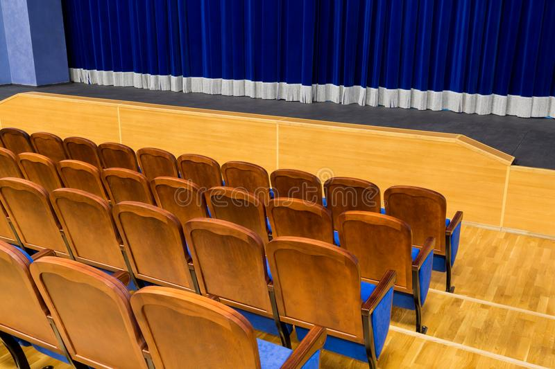 The auditorium in the theater. Blue curtain on the stage. Blue-brown chair. Room without people stock photography