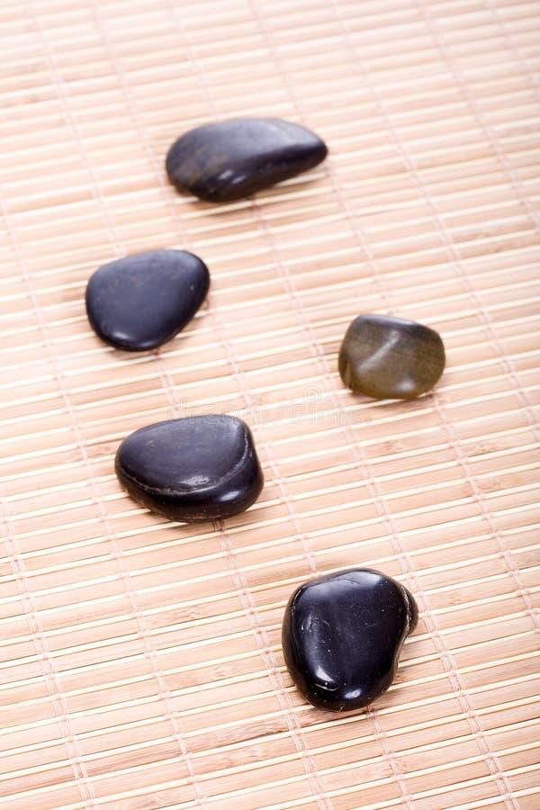 Auf Bambusmatte di Zen-Steine immagini stock libere da diritti