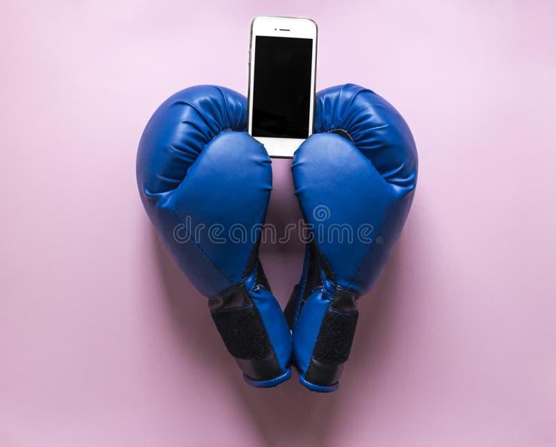 Auf Boxhandschuhen eines rosa Hintergrundes zwei der blauen Farbe in Form eines Herzens mit einem Telefon in den Händen stockbilder