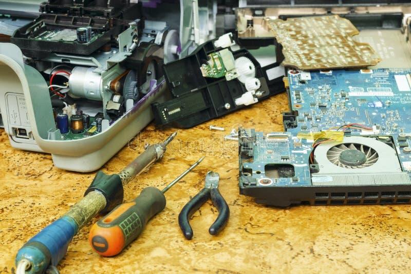 Auf dem Desktop ist auseinandergebaute Ausrüstung und Werkzeuge für Reparatur stockfotografie