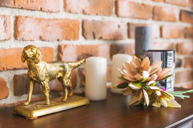 Auf dem hölzernen Aufbereiter gibt es eine goldene Statuette eines Hundes und eines anderen Dekors stockfoto