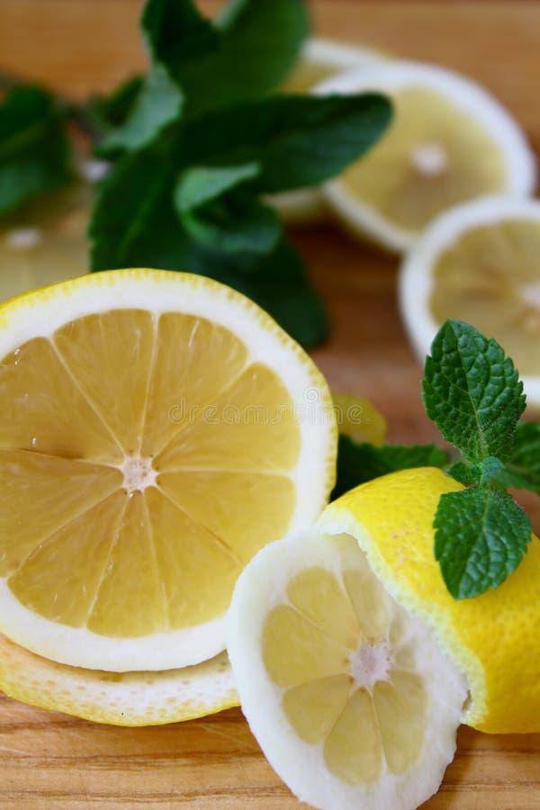 Auf dem hackenden Vorstand Gelbe Zitrone mit frischem Zweig der Minze lizenzfreie stockbilder