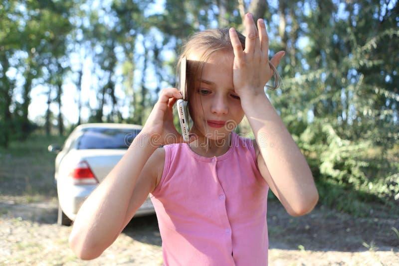 Auf dem Hintergrund der Natur ein kleines Mädchen, das emotional am Telefon spricht stockfotografie