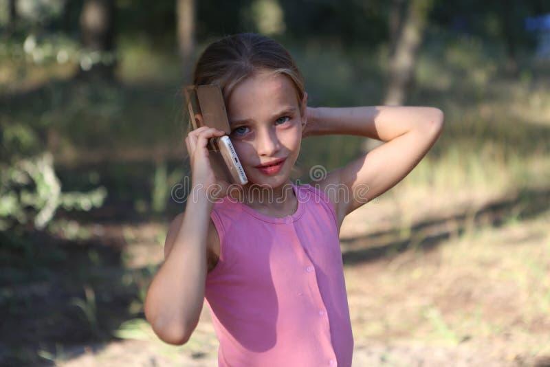 Auf dem Hintergrund der Natur ein kleines Mädchen, das emotional am Telefon spricht stockfoto