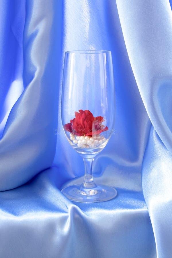 auf dem Hintergrund des blauen silk Drapierung ist ein hohes Glas auf einem dünnen lizenzfreie stockbilder