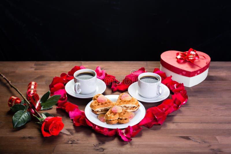 Auf dem Holztisch innerhalb des Herzens der rosafarbenen Blumenblätter sind zwei Tasse Kaffees und eine Platte mit Keksen Draußen stockfoto