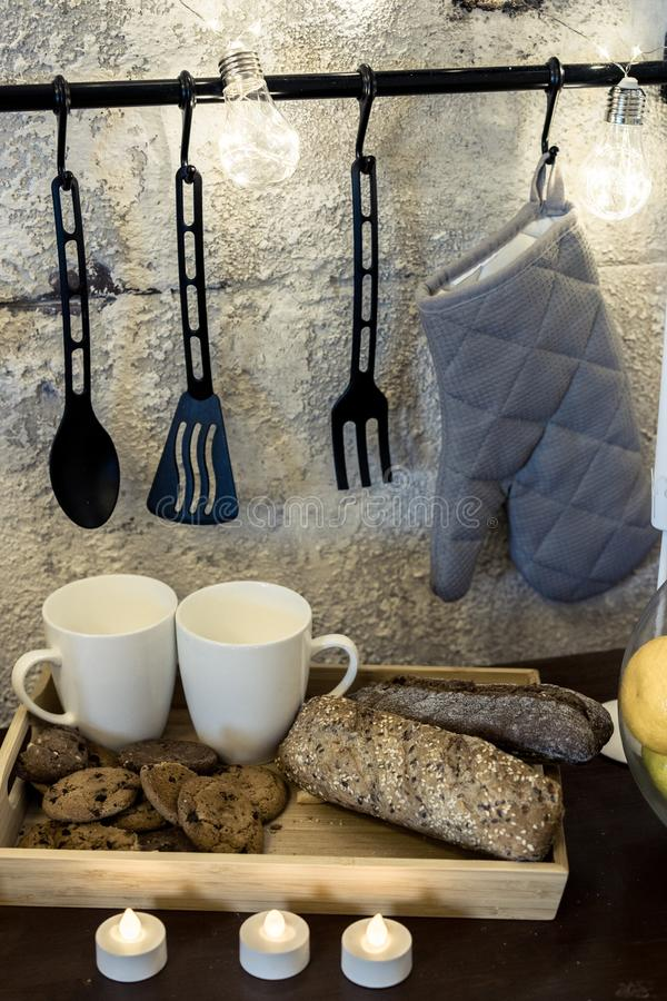 Auf dem Küchentisch vor einer konkreten grauen Wand sind weiße Pfeifen ein Girlande hängender Topfhalter WarteValentinsgrußes lizenzfreie stockfotografie