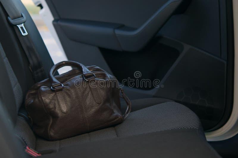 Auf dem Rücksitz des Autos ist eine braune Ledertasche auf dem Hintergrund der angelehnten Tür vergessen stockfoto