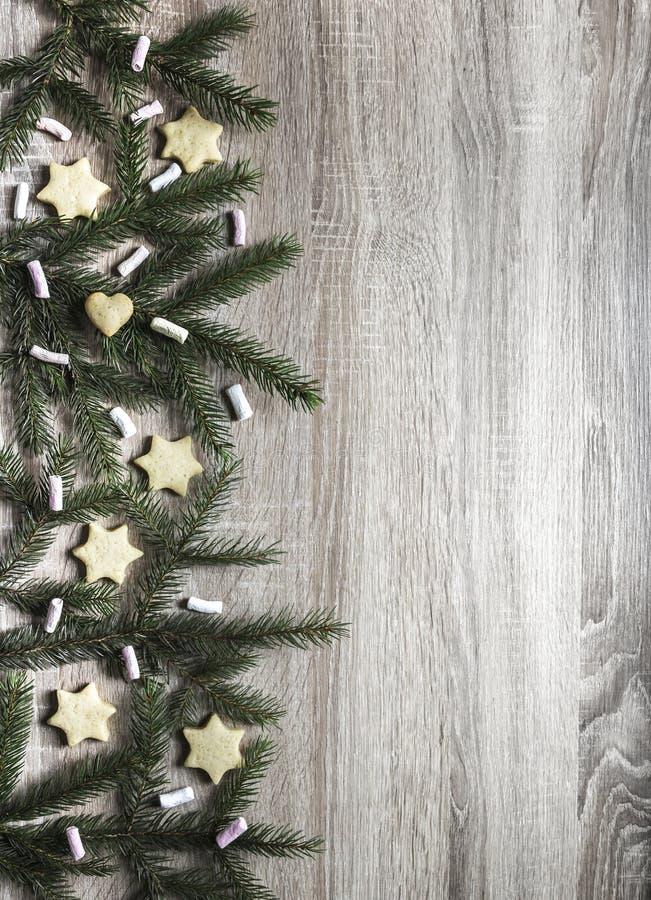 Auf dem Recht auf einem Holztisch sind Fichtenzweige und Eibische, Ingwerkekse in Form von Sternchen und ein Herz lizenzfreies stockbild
