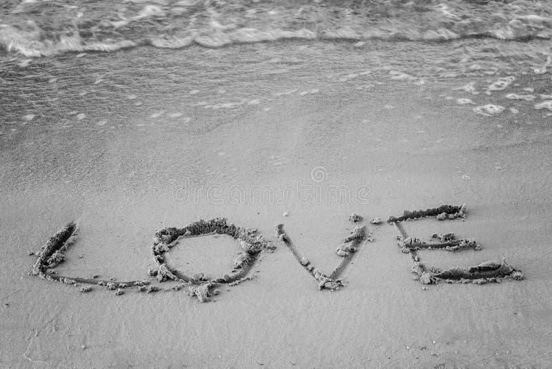 Auf dem Sand bewegen schriftliches Wort und seine Liebeswäschen wellenartig, Schwarzweiss lizenzfreie stockbilder