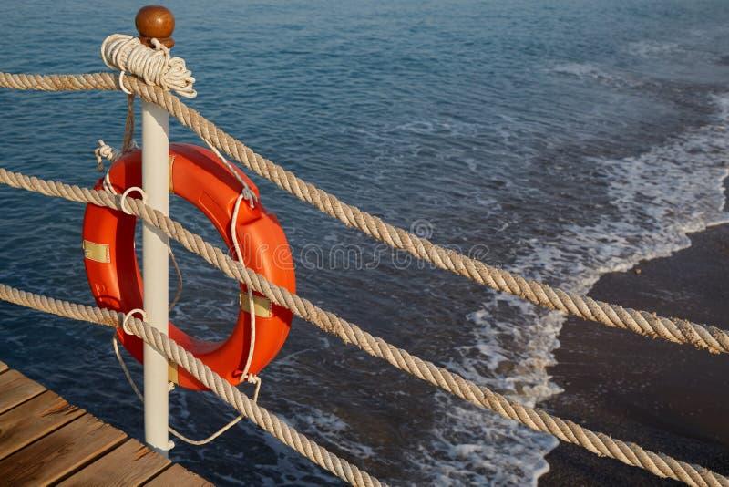 Auf dem Strand gibt es ein Rettungswerkzeug für Ertrinkender in Form einer Lebenboje mit einem Seil stockfotos