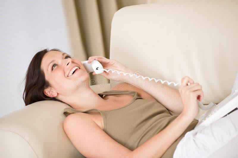 Auf dem Telefonhaus: Frau, die sich auf Sofa hinlegt stockbilder