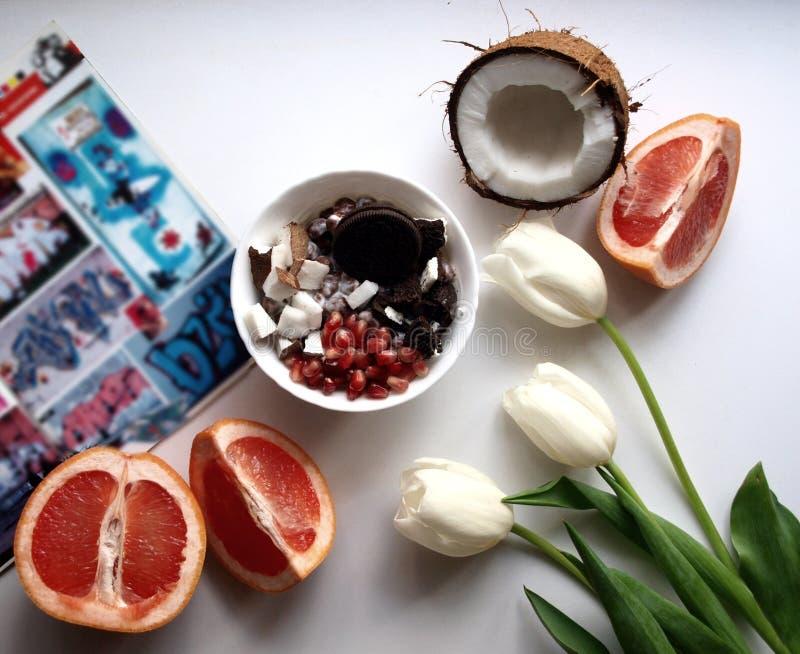 Auf dem Tisch eine Zeitschrift, eine Stunde mit Frühstück und Bonbons, Früchte und Blumen, Kokosnuss und Pampelmuse Sommer entspa stockbild