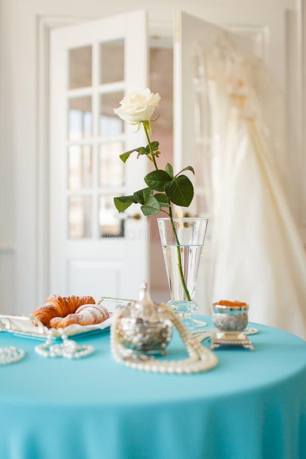 Auf dem Tisch in einer weißen Rose und in den Dekorationen des Vase stockfotografie