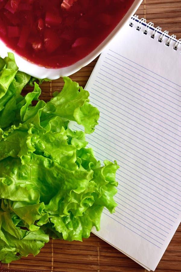 Auf dem Tisch ist ein Teil einer Schüssel Suppe, legt die Blätter des Kopfsalates und des Notizbuches lizenzfreies stockbild