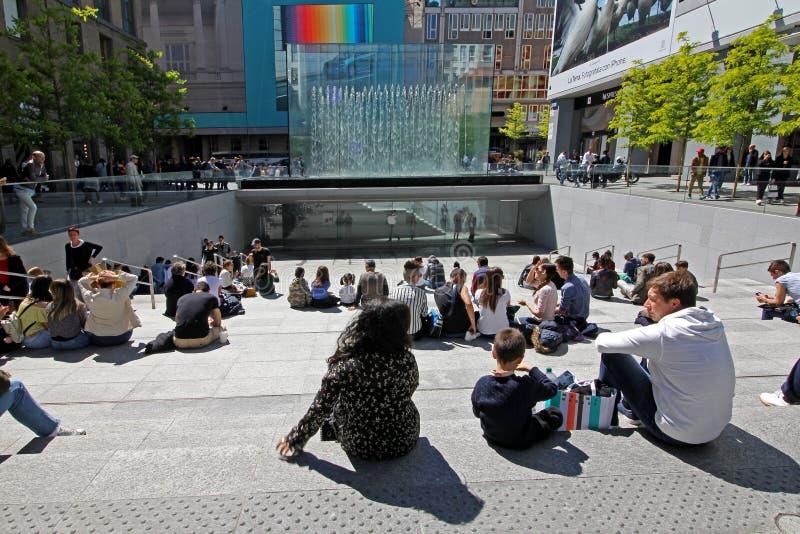 Auf dem Treppenhaus das Kristallparallelepiped Apple Stores in der Marktplatz-Freiheit in Mailand bewundernd stockfotografie