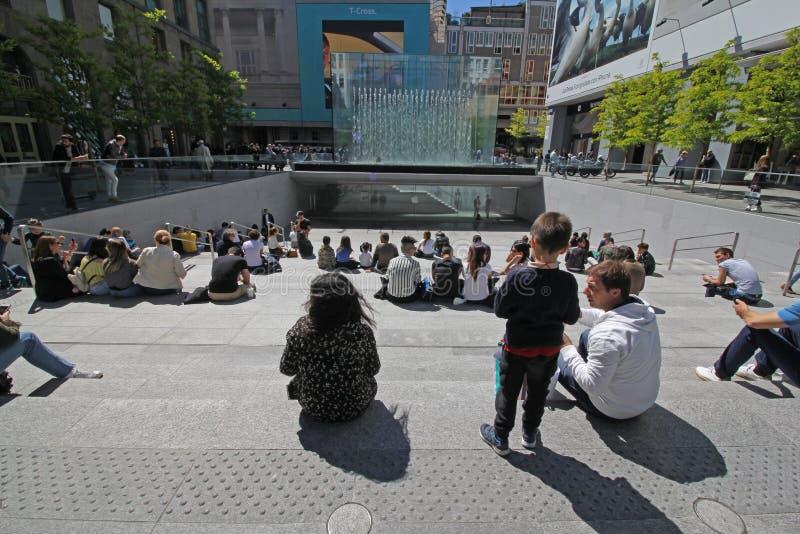 Auf dem Treppenhaus das Kristallparallelepiped Apple Stores in der Marktplatz-Freiheit in Mailand bewundernd stockbild