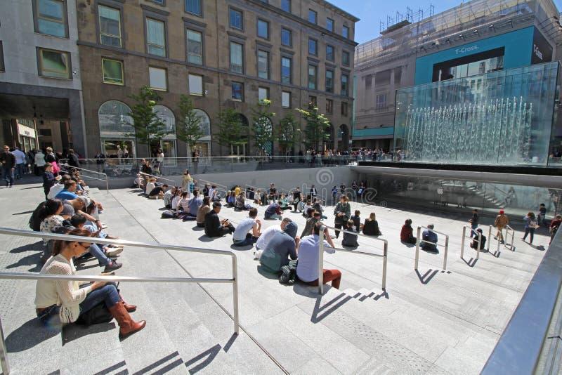 Auf dem Treppenhaus das Kristallparallelepiped Apple Stores in der Marktplatz-Freiheit in Mailand bewundernd lizenzfreies stockfoto