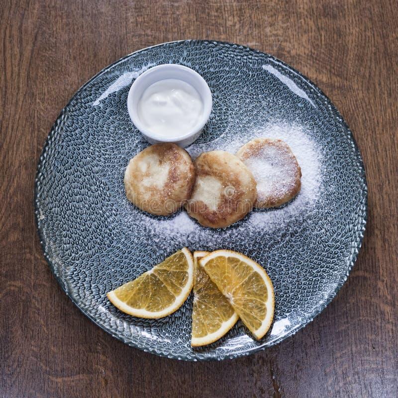 Auf der Platte sind drei Käsekuchen, besprüht mit pulverisiertem sug lizenzfreies stockbild