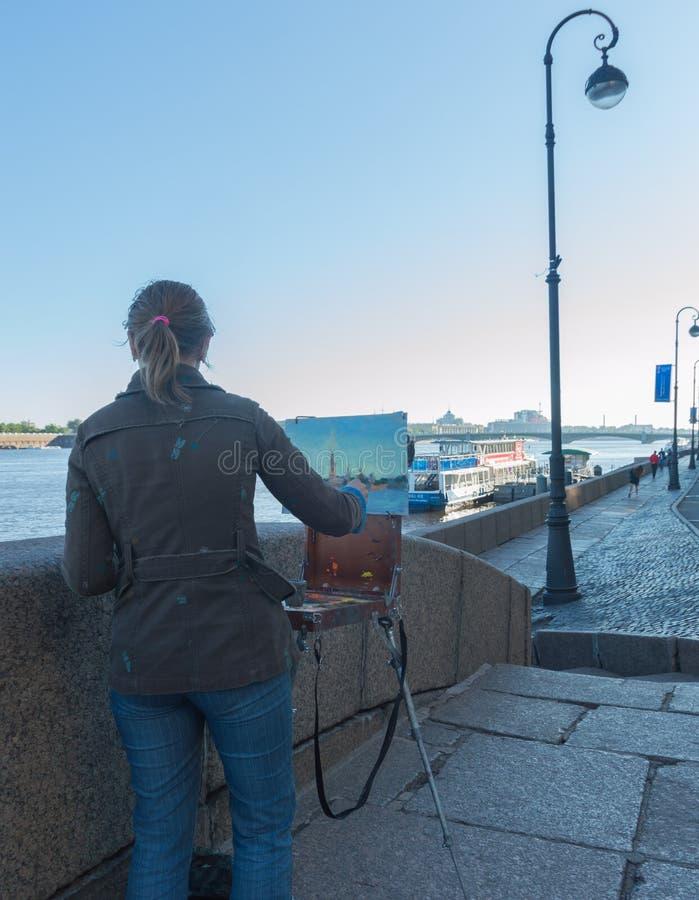 Auf der Ufergegend zeichnet ein Bild eines Mädchenkünstlers lizenzfreie stockfotografie