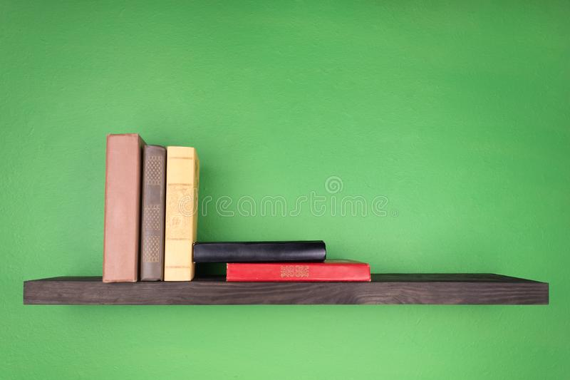 Auf der Wand der grünen Farbe gibt es ein dunkles hölzernes Regal mit einer Beschaffenheit, auf der einige Bücher vertikal vom li stockbild