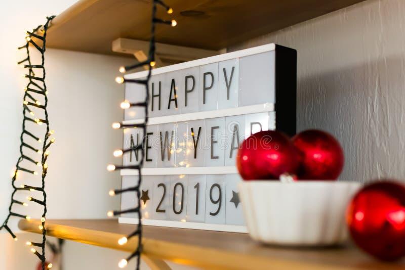 Auf der weißen Anzeige des hölzernen Regals in den gotischen Schriften das neue Jahr 2019 der Aufschrift Girlande und rote Weihna lizenzfreies stockfoto
