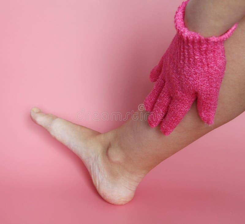 Auf der weiblichen Hand, die einen rosa Handschuh trägt, um den Körper zu waschen stockbild