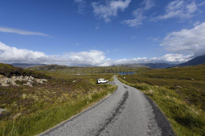 Auf eine einsame Straße durch das schöne schottische Heidemoor fahren, Assynt, Schottland, Großbritannien lizenzfreie stockbilder