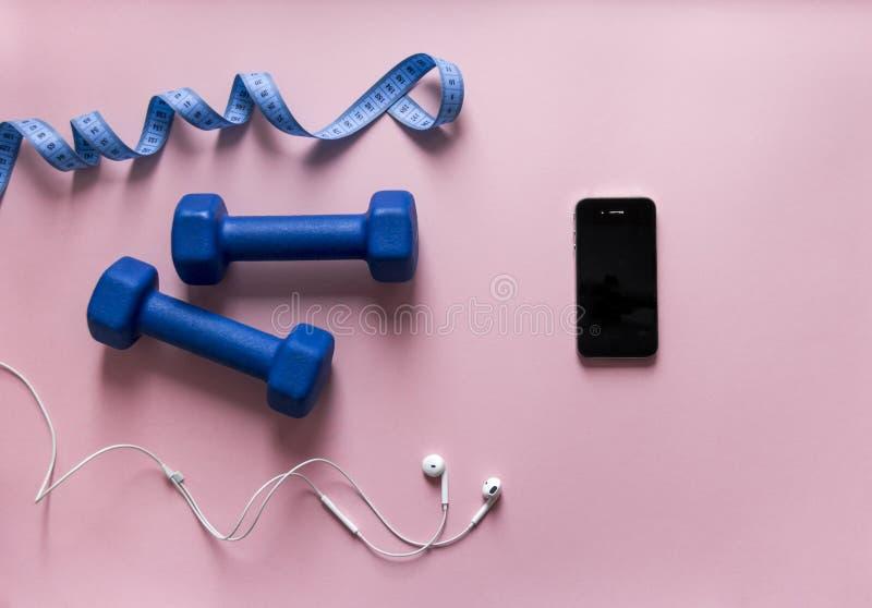 Auf einem Bandzentimeter-Telefon Smartphone des rosa Hintergrundboxhandschuhs blauen Farbmit den Kopfhörern weiß stockbild