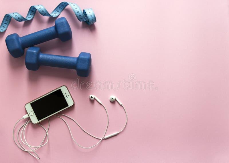 Auf einem Blau und fliegenden einem Zentimeter der Rosahintergrunddummköpfe stellen Sie weiches Licht Sportkopfhörermusiktelefon  lizenzfreies stockbild