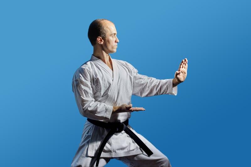 Auf einem blauen Hintergrund führt ein Athlet mit einem schwarzen Gürtel eine formale Karateübung durch stockbild