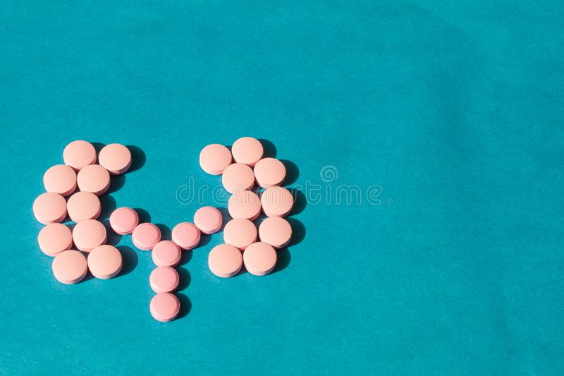 Auf einem blauen Hintergrund von den Tabletten wird die Form von menschlichen Nieren ausgebreitet Das Konzept einer Heilung für d lizenzfreies stockfoto