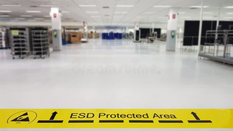 Auf einem Boden der Elektronik bedeckte die Herstellung industrielles Linoleum klebt ein gelbes Band mit einem warnenden Standard lizenzfreie stockfotografie