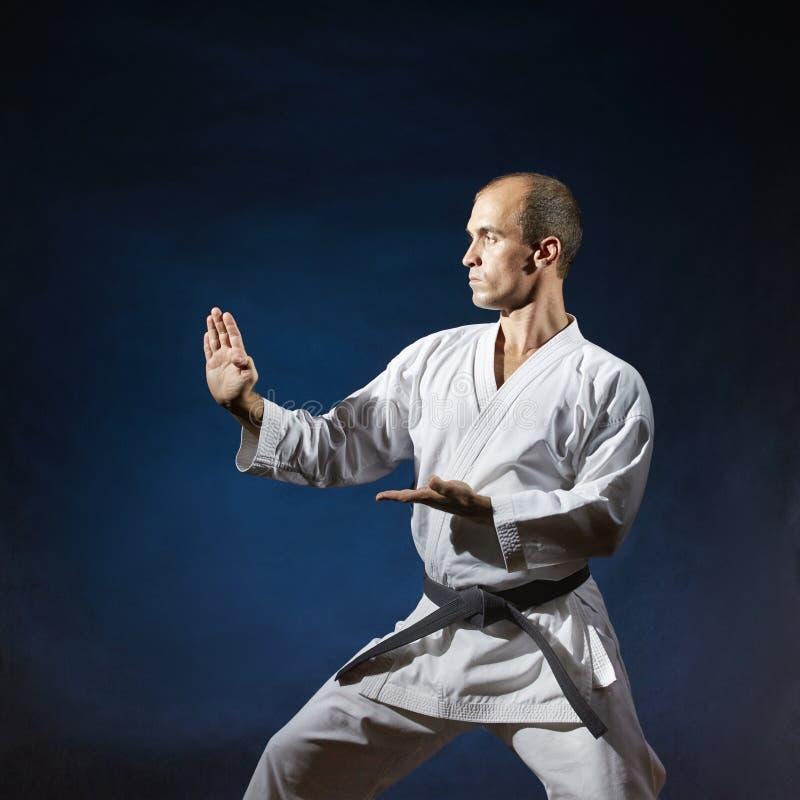 Auf einem dunkelblauen Hintergrund führt ein Athlet mit einem schwarzen Gürtel formale Karateübungen durch stockfotos