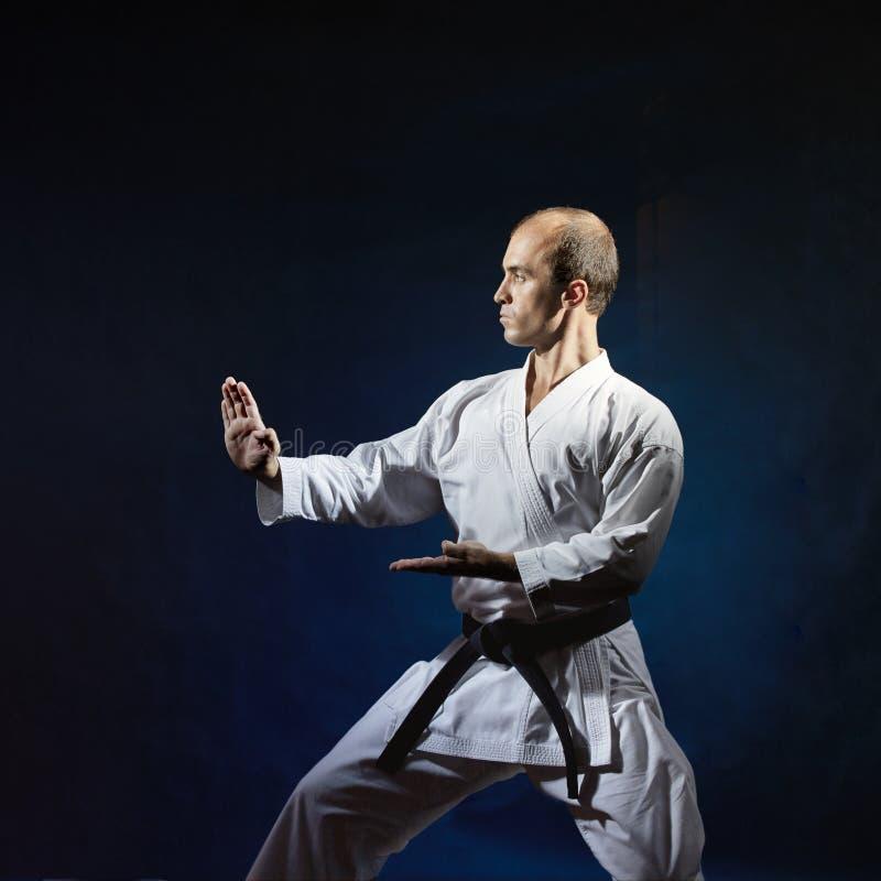 Auf einem dunkelblauen Hintergrund trägt ein Erwachsener eine formale Karateübung zur Schau stockfoto