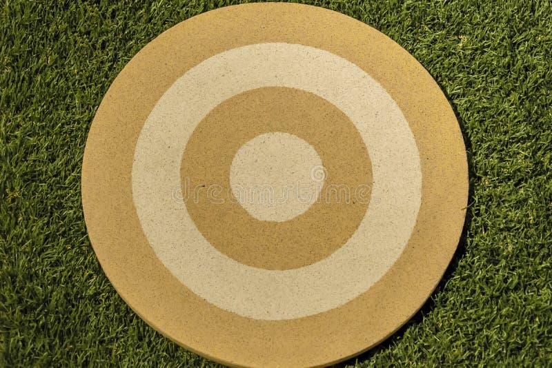 Auf einem Grashintergrund wird das Ziel mit Kreisen in goldene Töne gelegt stockfoto