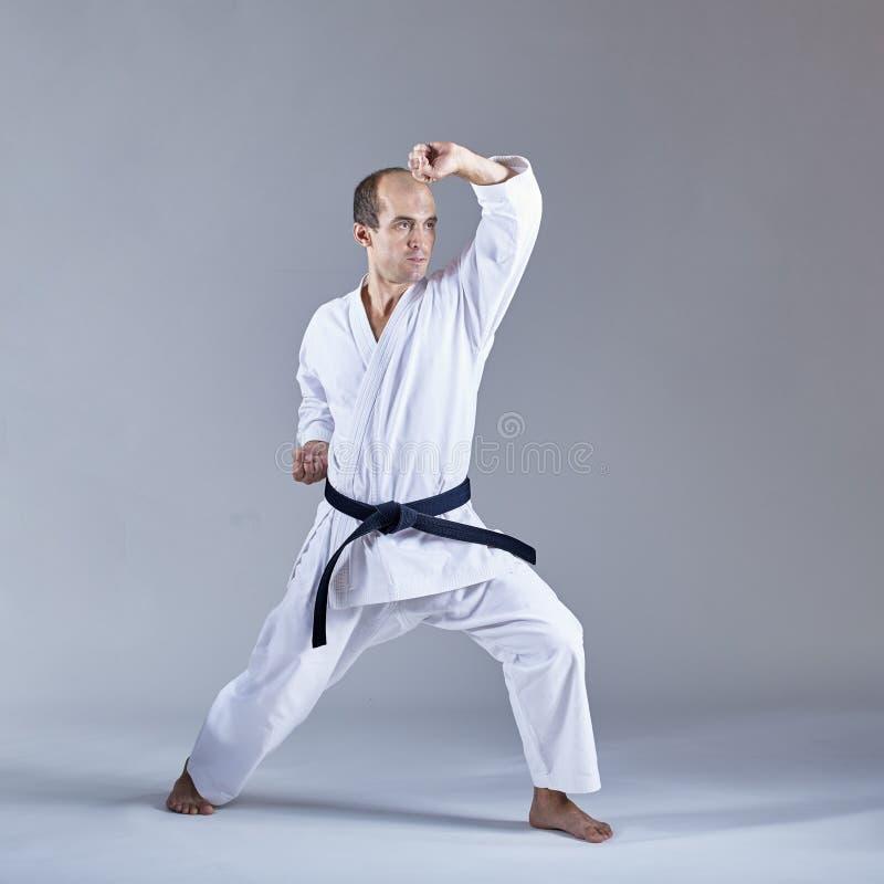 Auf einem grauen Hintergrund bildet der Athlet den Block mit seiner Hand in einer formalen Karateübung aus stockbilder