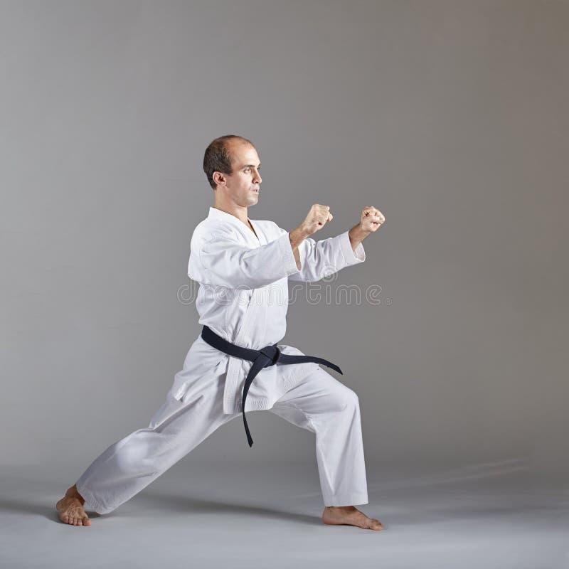 Auf einem grauen Hintergrund bildet ein Athlet mit einem schwarzen Gürtel eine formale Karateübung aus lizenzfreies stockfoto