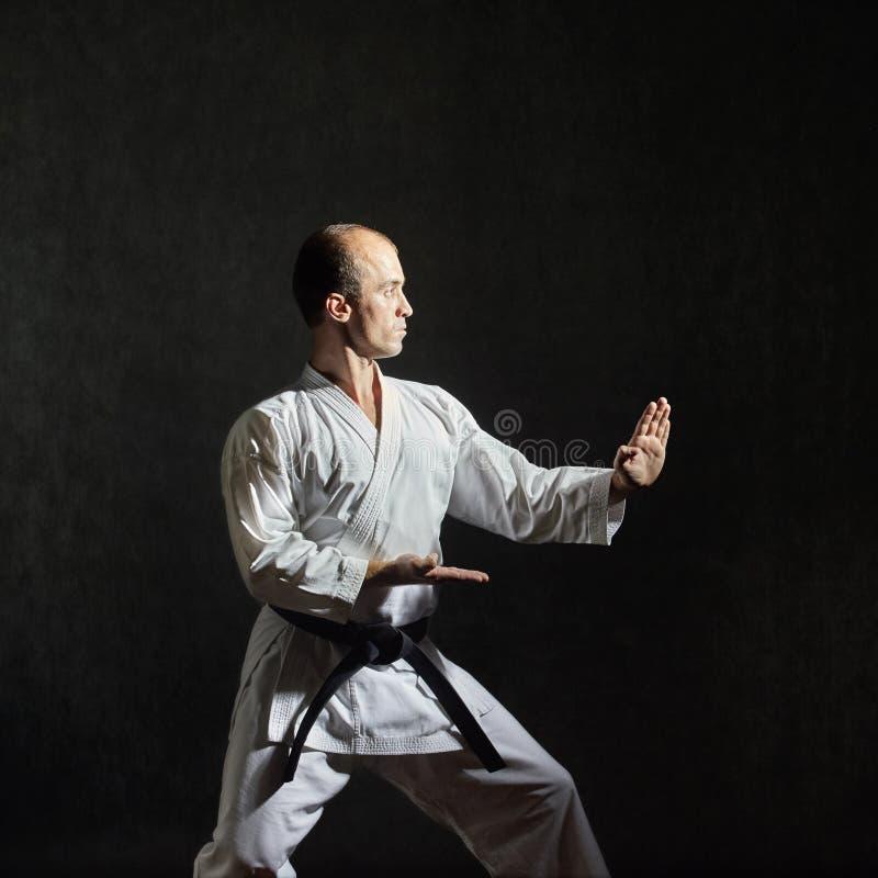 Auf einem grauen Hintergrund bildet ein Athlet mit einem schwarzen Gürtel ein formales Übungskarate aus stockbilder