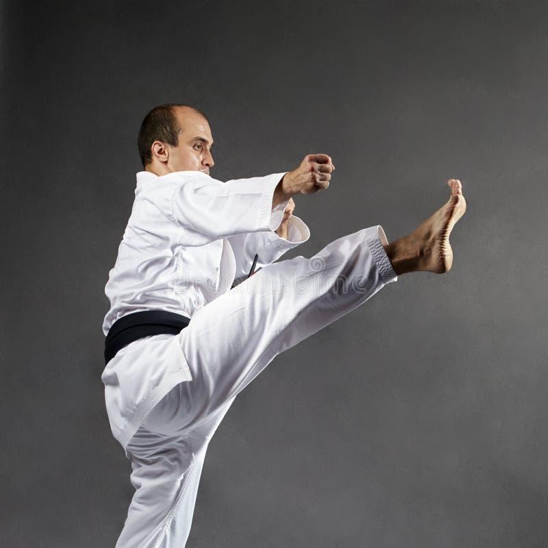 Auf einem grauen Hintergrund treten die Athletenschläge Bein im karategi lizenzfreie stockfotografie