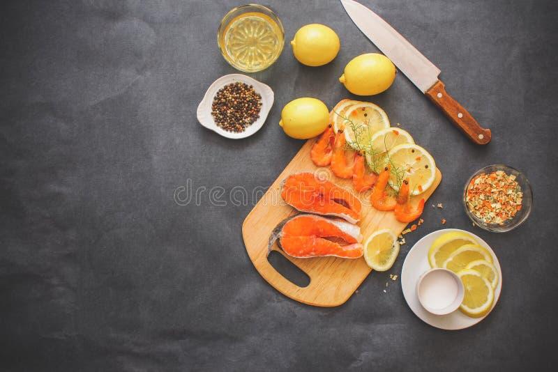 Auf einem hölzernen Brett breitete rohen Garnelengrünzitronenscheibensalz-Gewürzlachspfeffer und ein Messer für das Kochen aus stockbilder
