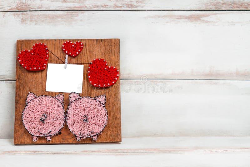 Auf einem hölzernen Hintergrund gibt es eine handgemachte Platte mit dem Bild von zwei Schweinen und von Herzen Kopieren Sie Plat stockfoto