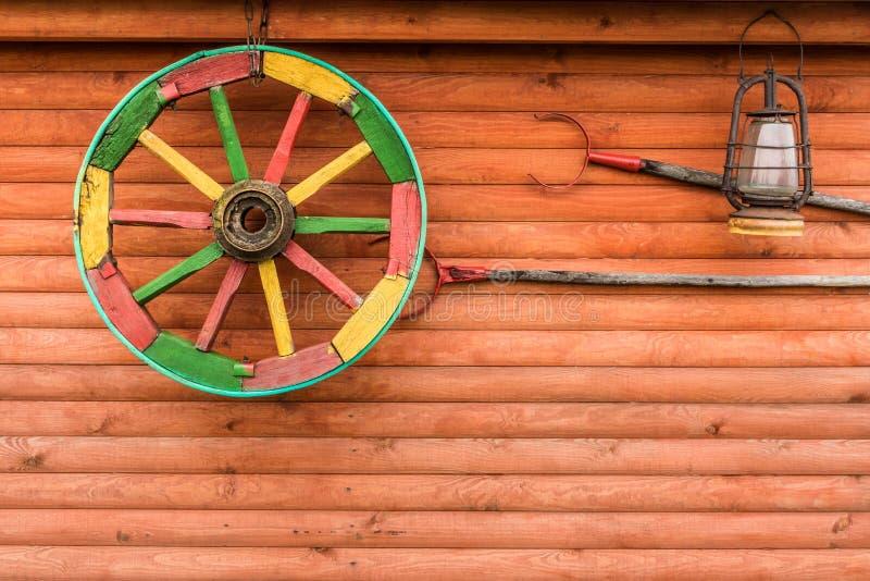 Auf einem hölzernen Wandbehang gemaltes Wagenrad, Zangen für Topf und La lizenzfreies stockbild